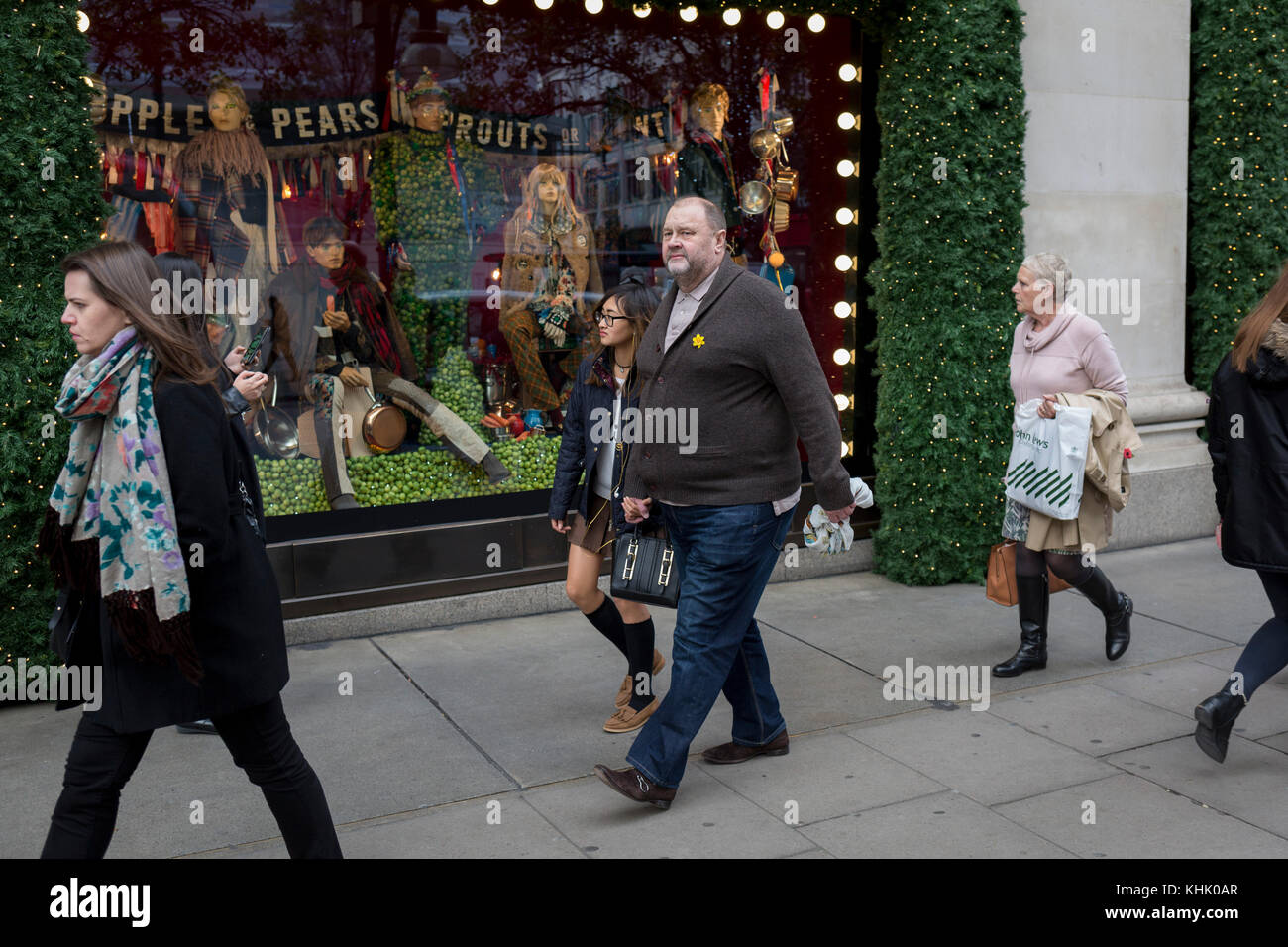 Young girl holds hands with an older man outside Selfridges, on 9th November 2017, London, England. - Stock Image