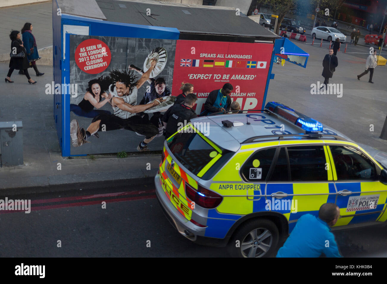 Met police officers question a man next to the poster for Stomp, the West End musical production, on 13th November - Stock Image