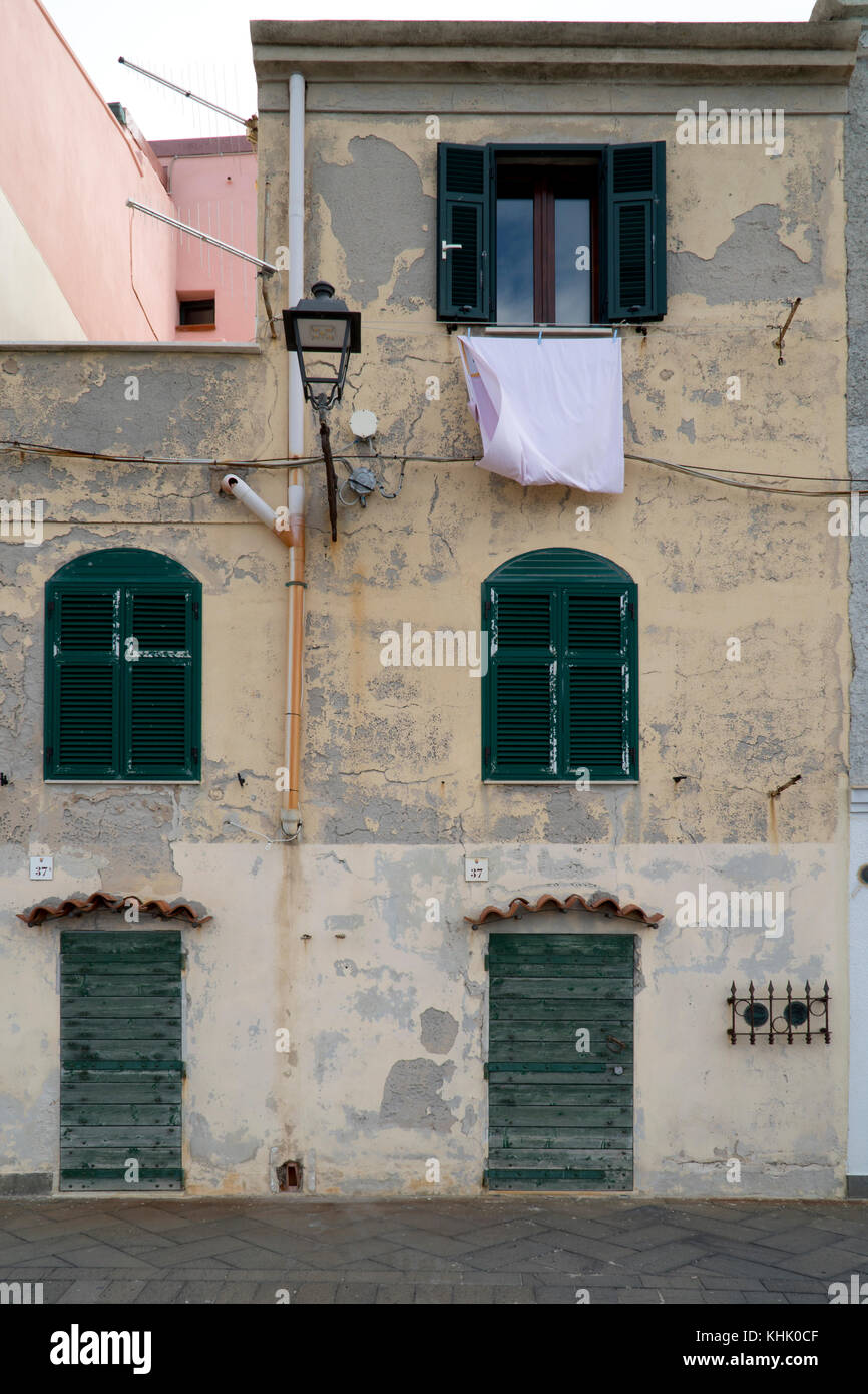 Street scene of narrow houses and washing hanging from a window with a street lamp outside shuttered windows, Sardinia. - Stock Image
