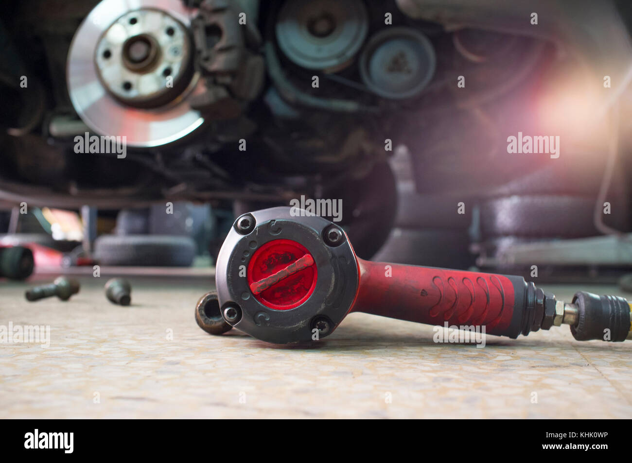 Pneumatic wrench screwing mechanic tool and knots with no wheel car at bottom - Stock Image