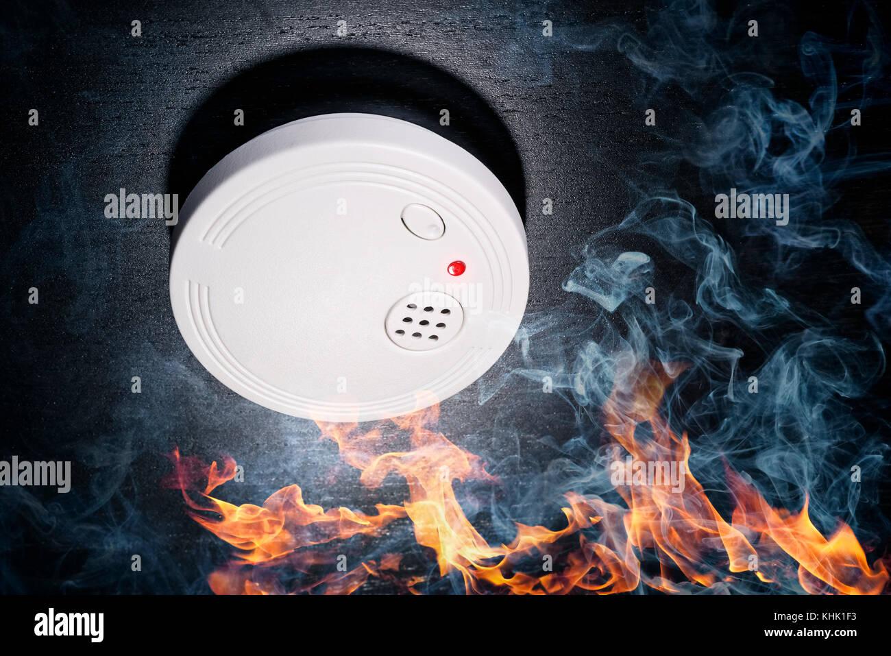 Smoke detector with flames and smoke - Stock Image