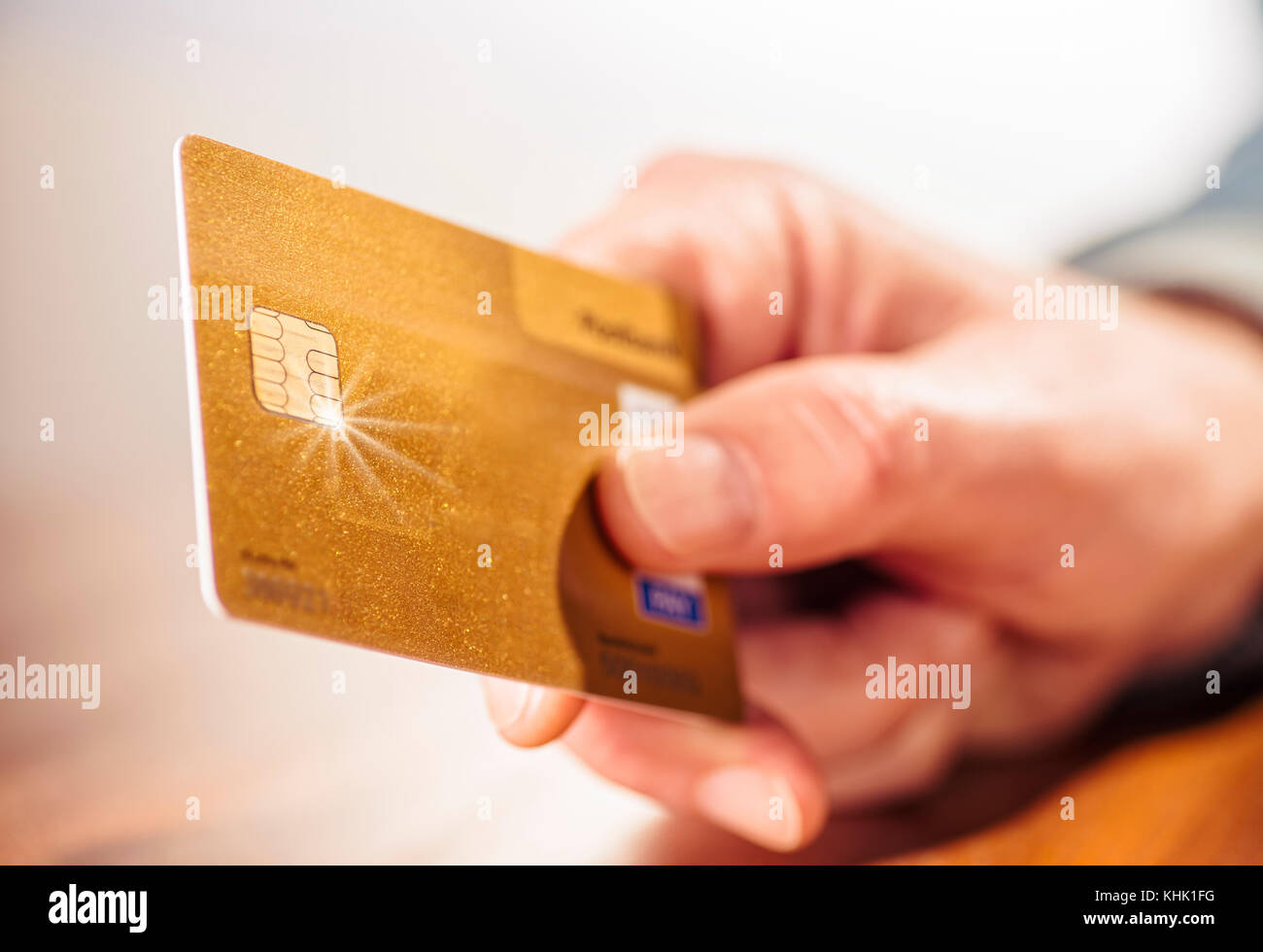 Closeup of a hand with a golden credit card - Stock Image