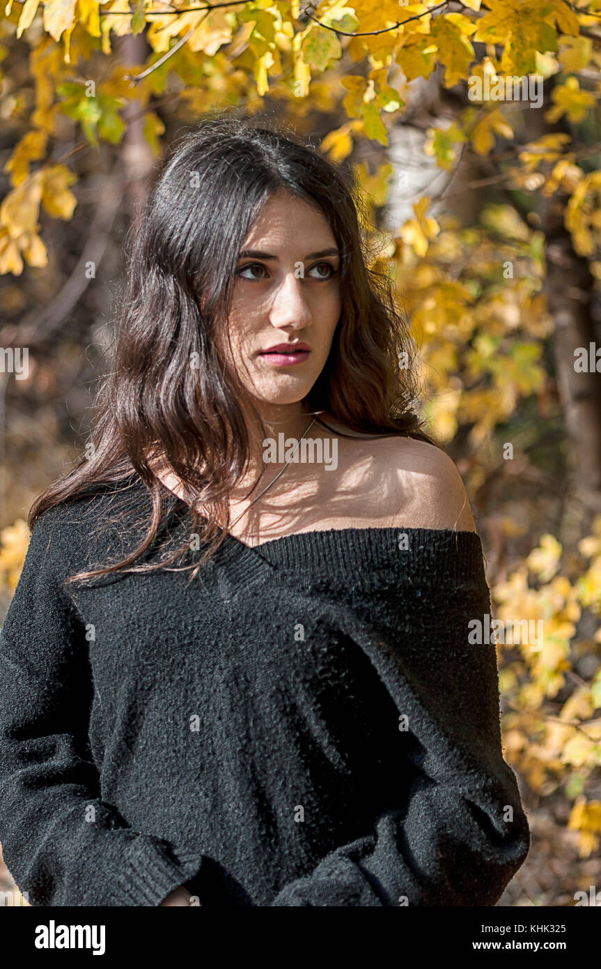 Portrait of a woman. Autumn yellow leaves. Bare shoulder. Real People. - Stock Image