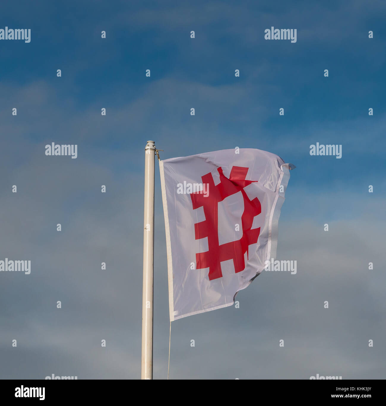 English Heritage flag flying from a flagpole against a blue sky background with copy space - Stock Image