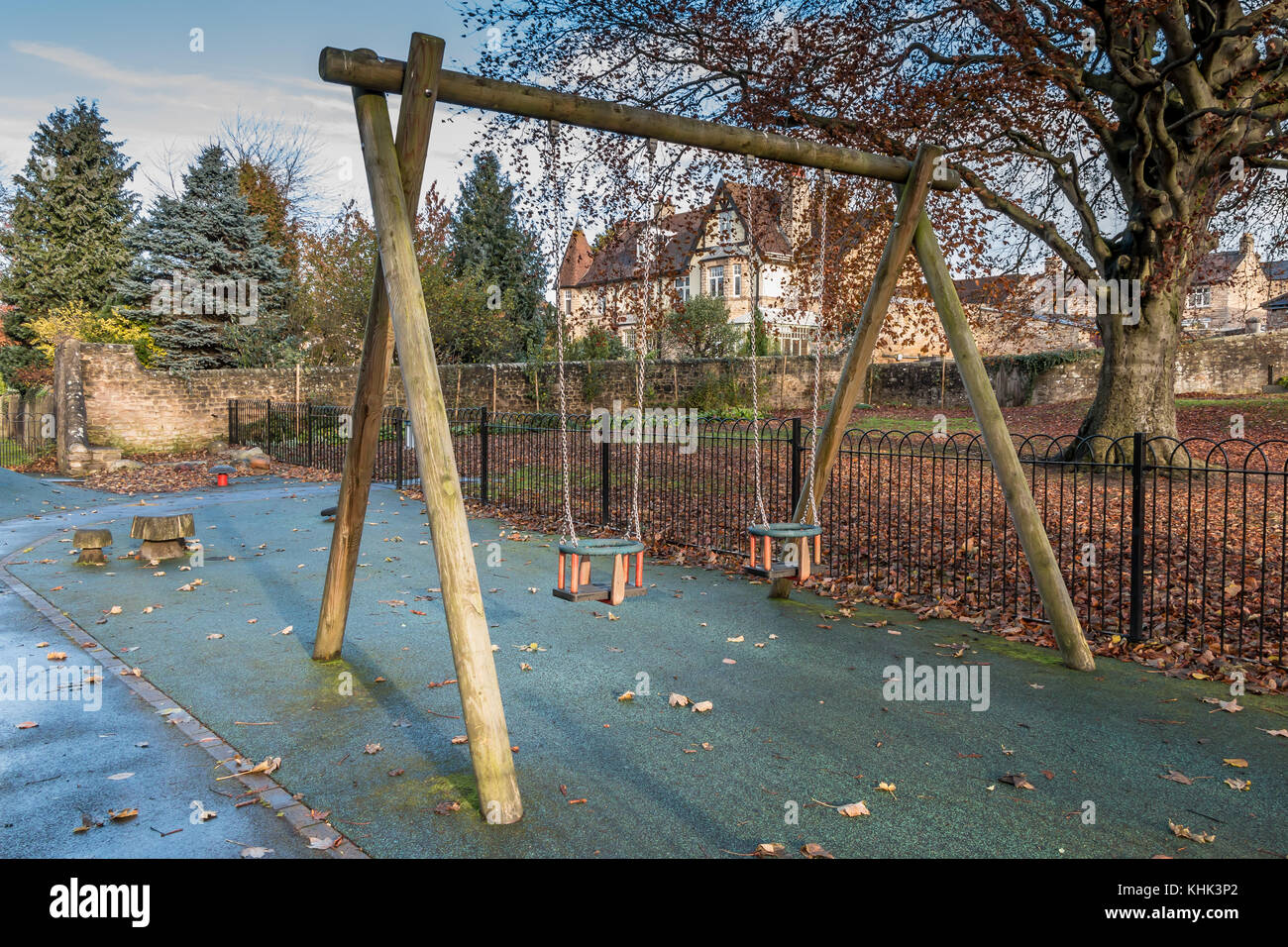 An unoccupied pair of children's swings in a play area closed for winter at Barnard Castle, North East England, - Stock Image