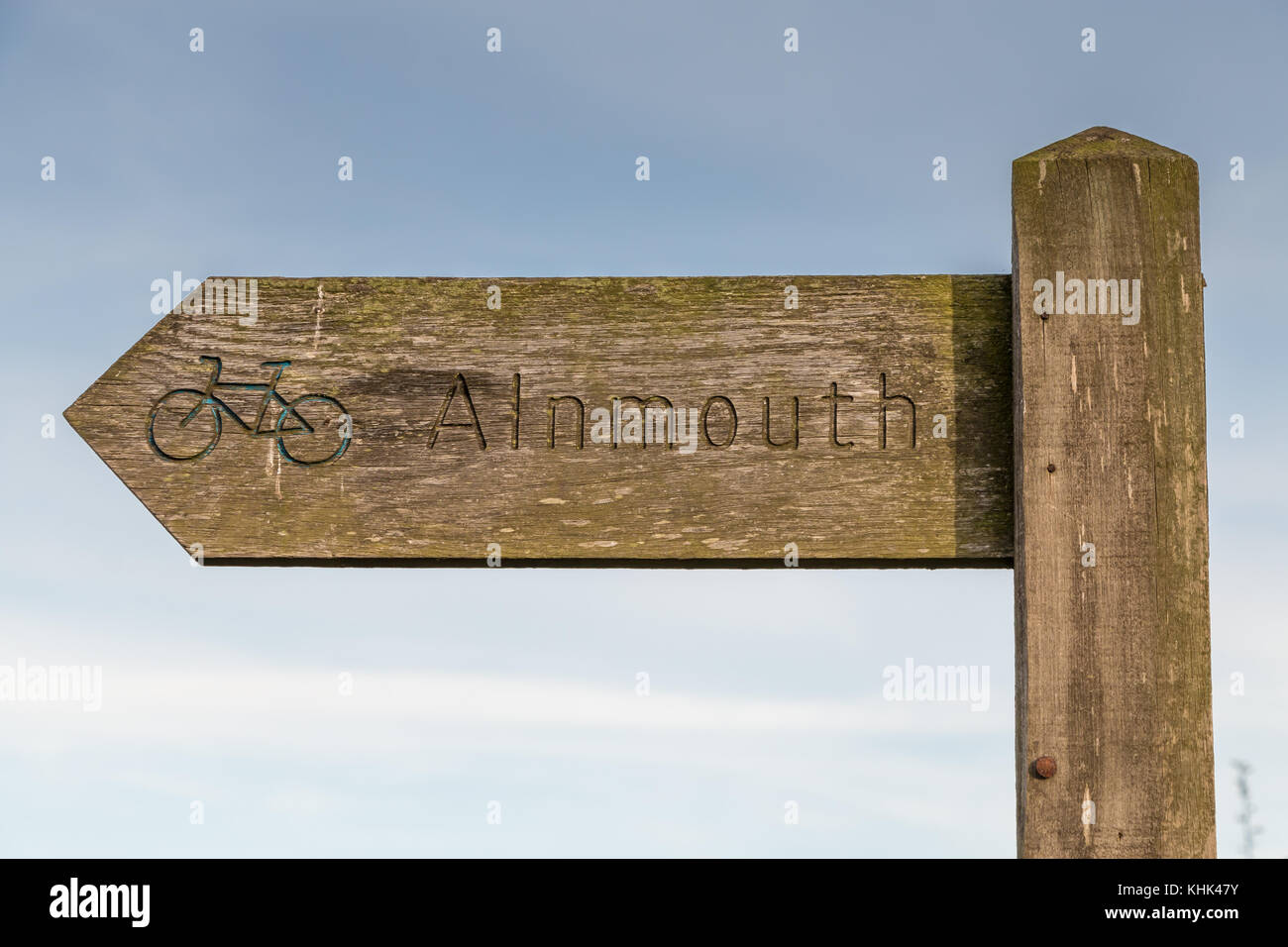 Wooden signpost with faded blue painted cycle emblem on the Northumberland Coastal Cycle Route, Alnmouth, UK - Stock Image
