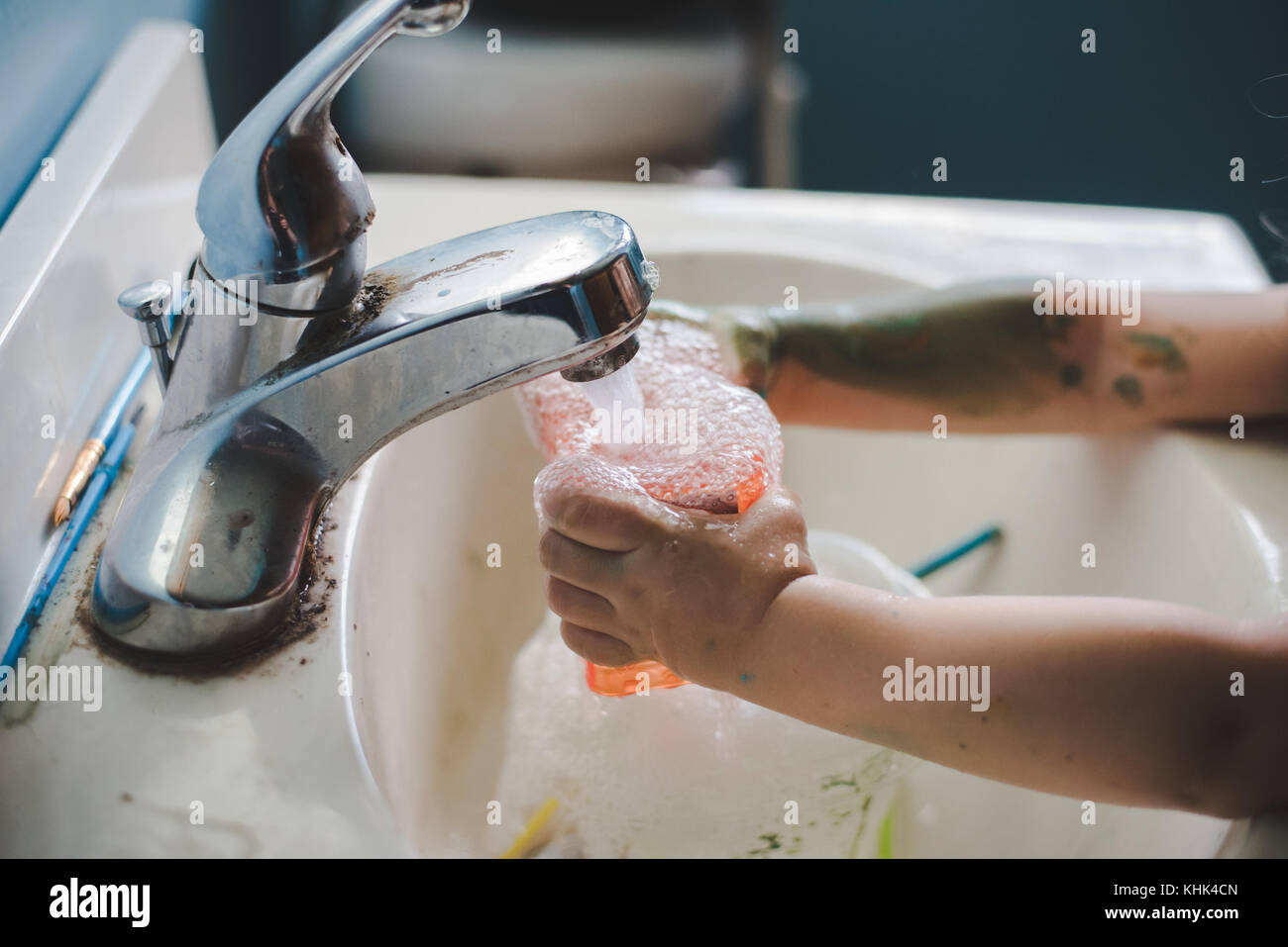 A toddler girl washing paint off her hands in a bathroom sink. Stock Photo