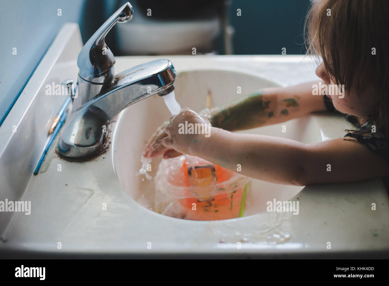 A toddler girl washing paint off her hands in a bathroom sink. - Stock Image