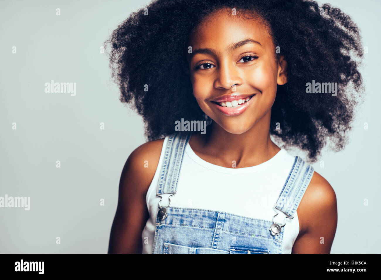 Cute Young African Girl With Long Curly Hair Smiling And Wearing