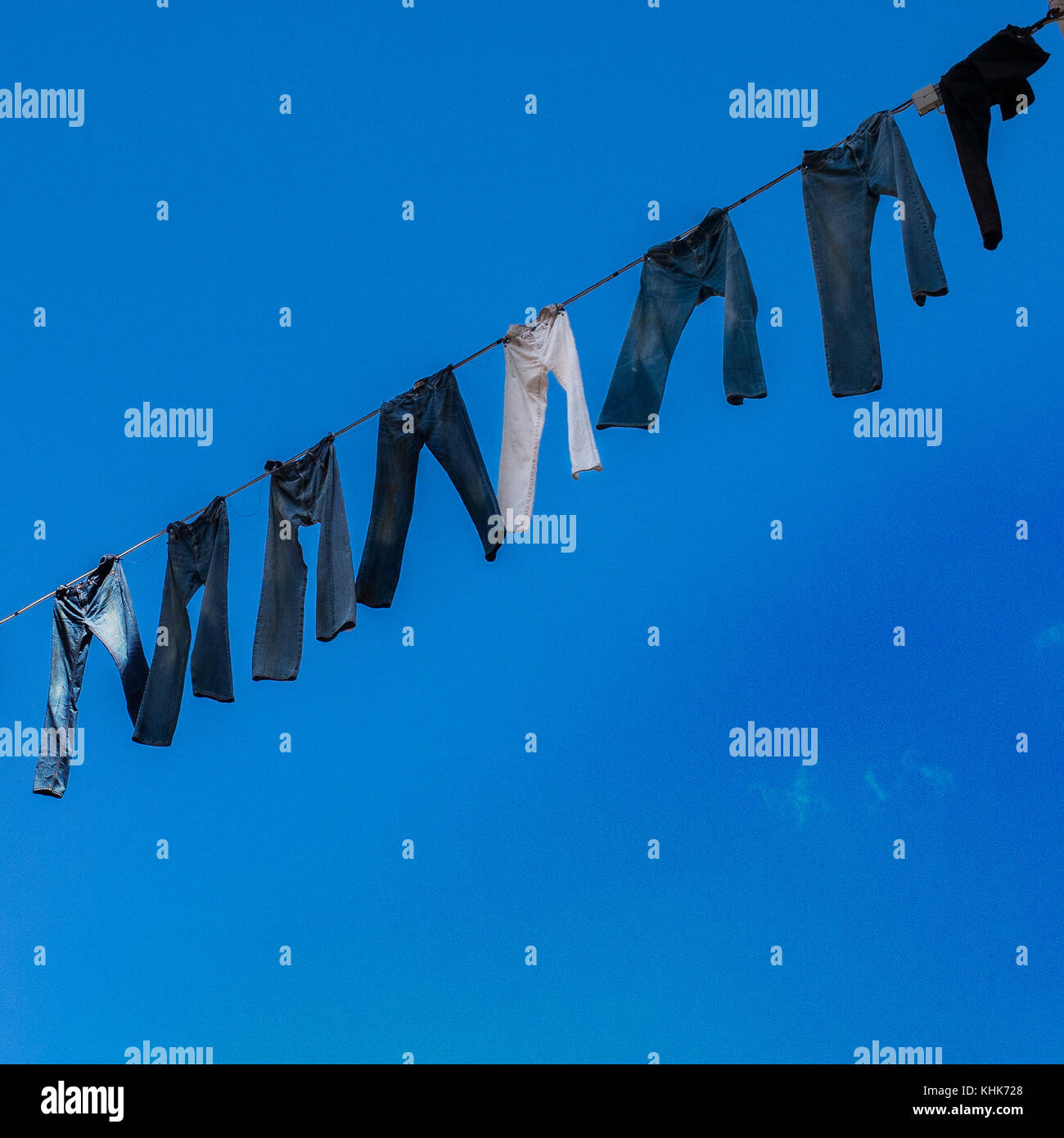 blue jeans hanging on line with the sky behind in Malmo Sweden - Stock Image