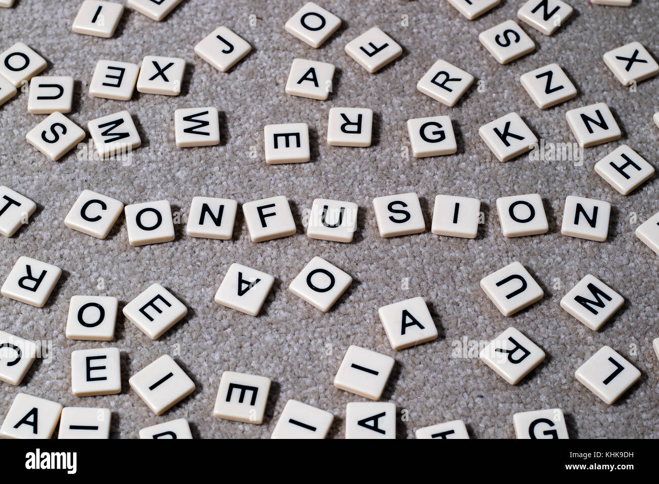 Confusion spelled out on scrabble style lettered tiles amongst a jumble of other letters. - Stock Image