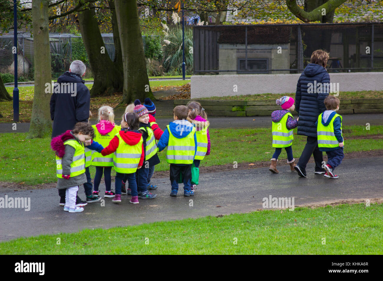 A children's playgroup in high visibility vests on a walk with adults through Ward Park in Bangor County Down - Stock Image