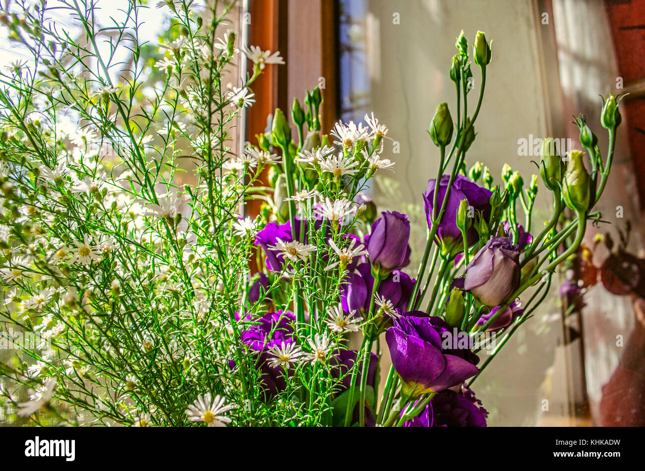 Bouquet of purple flowers Lisianthus with branches delicate white wildflowers on the windowsill in bright sunny - Stock Image