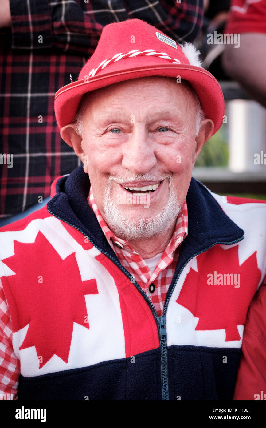 Portrait of male Canadian senior citizen celebrating Canada Day wearing a hat, red and white national colours, smiling - Stock Image