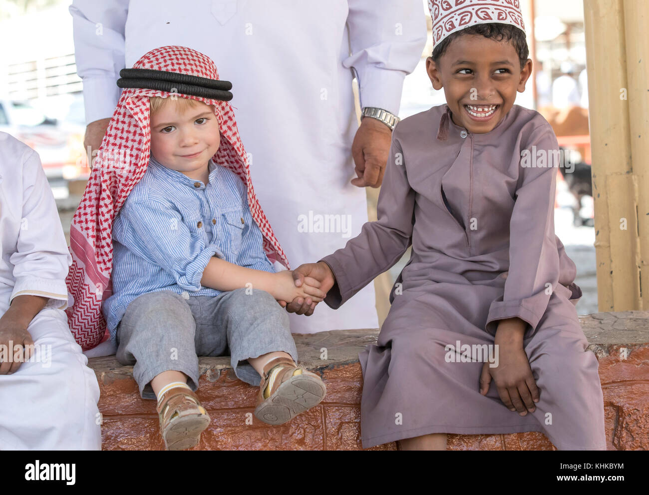 Nizwa, Oman, 10th Nobember 2017: omani kid and european kid shaking hands Stock Photo