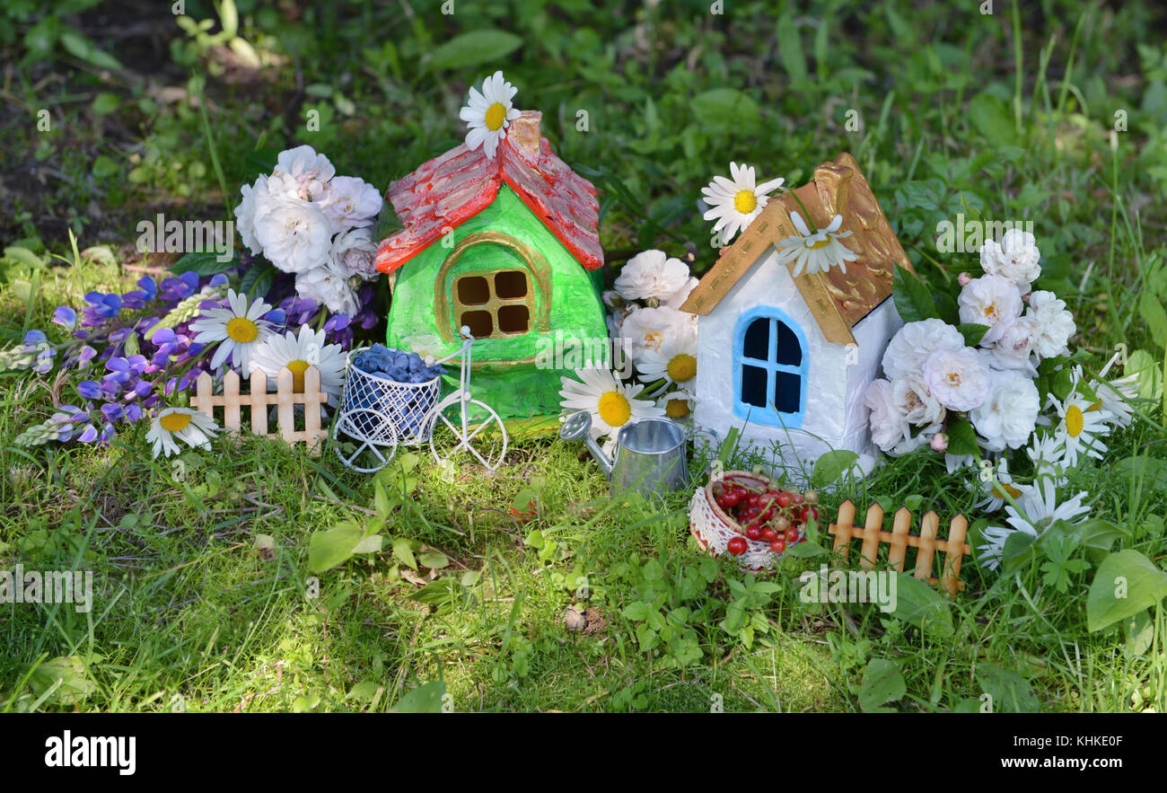 Two small beautiful houses with garden flowers and summer berries - Stock Image