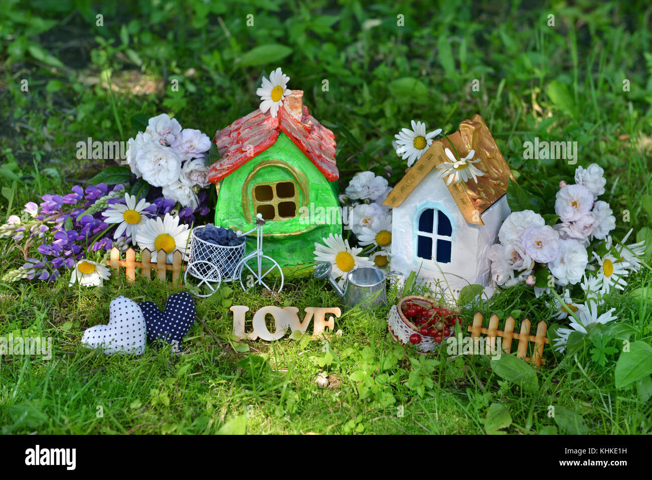 Two small toy houses with cute decorations, love letters, flowers, tiny fence and berries - Stock Image