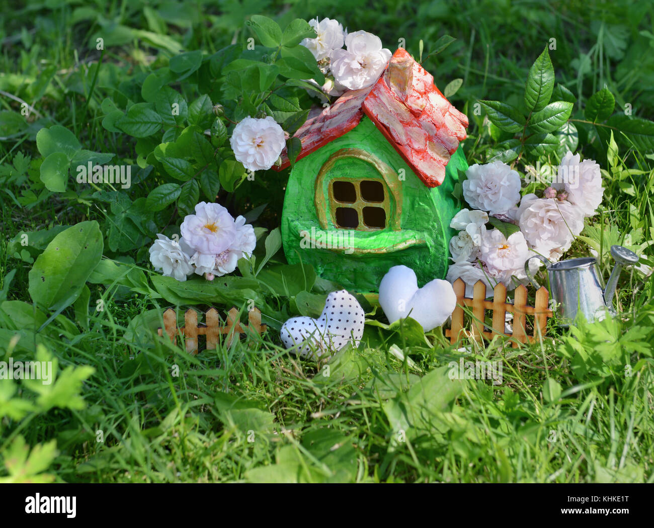 Small cute green house with roses, small fence, hearts and watering can in the garden - Stock Image