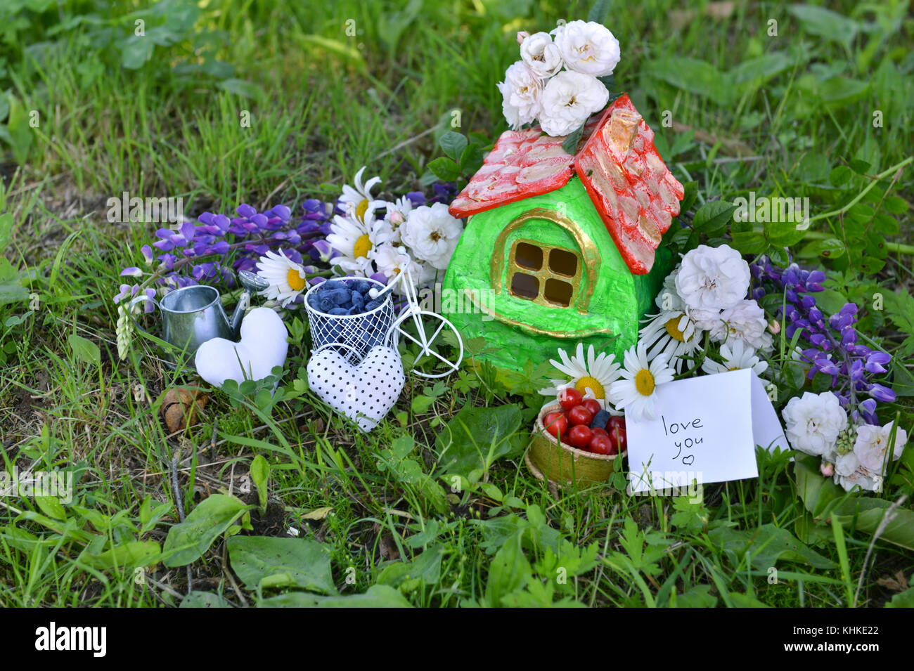 Small house with note love you, summer berries and flowers on the grass in the garden - Stock Image