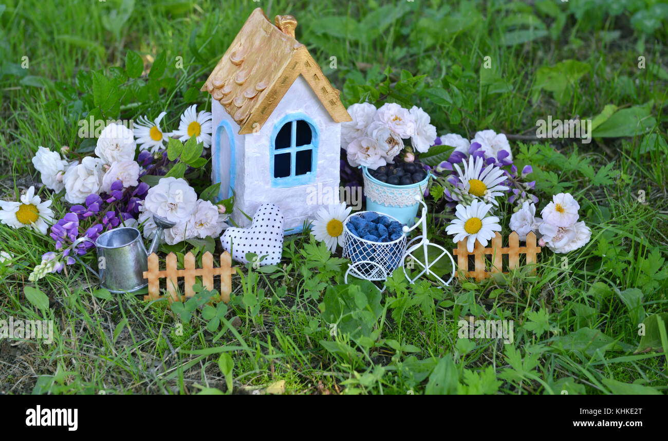 Beautiful tiny white house with wildflowers, roses, cute fence and watering can in the grass - Stock Image