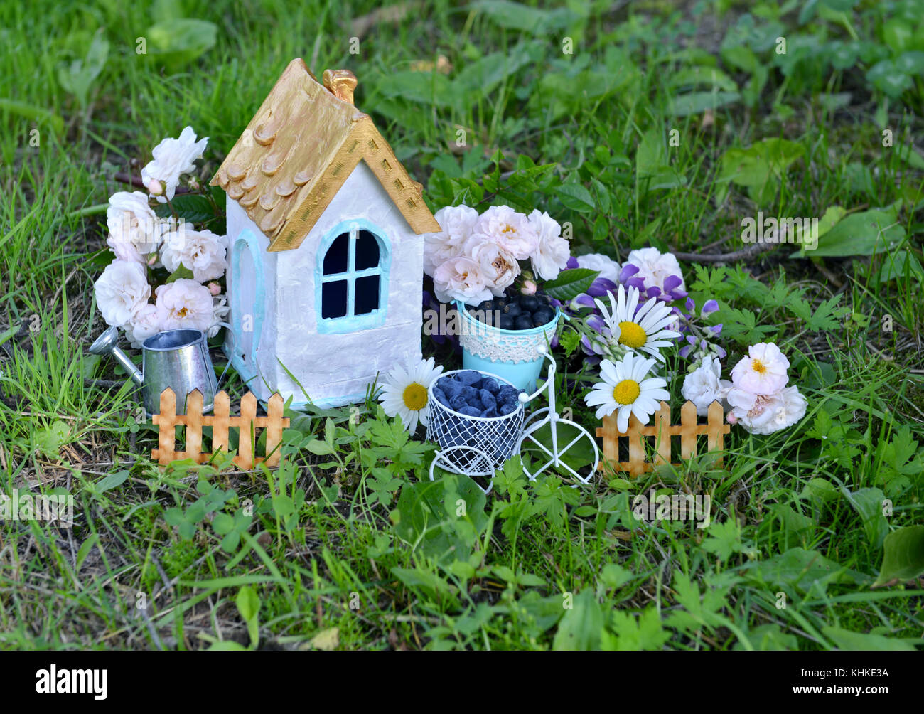 Small white house with roses and daisy flowers in the garden - Stock Image