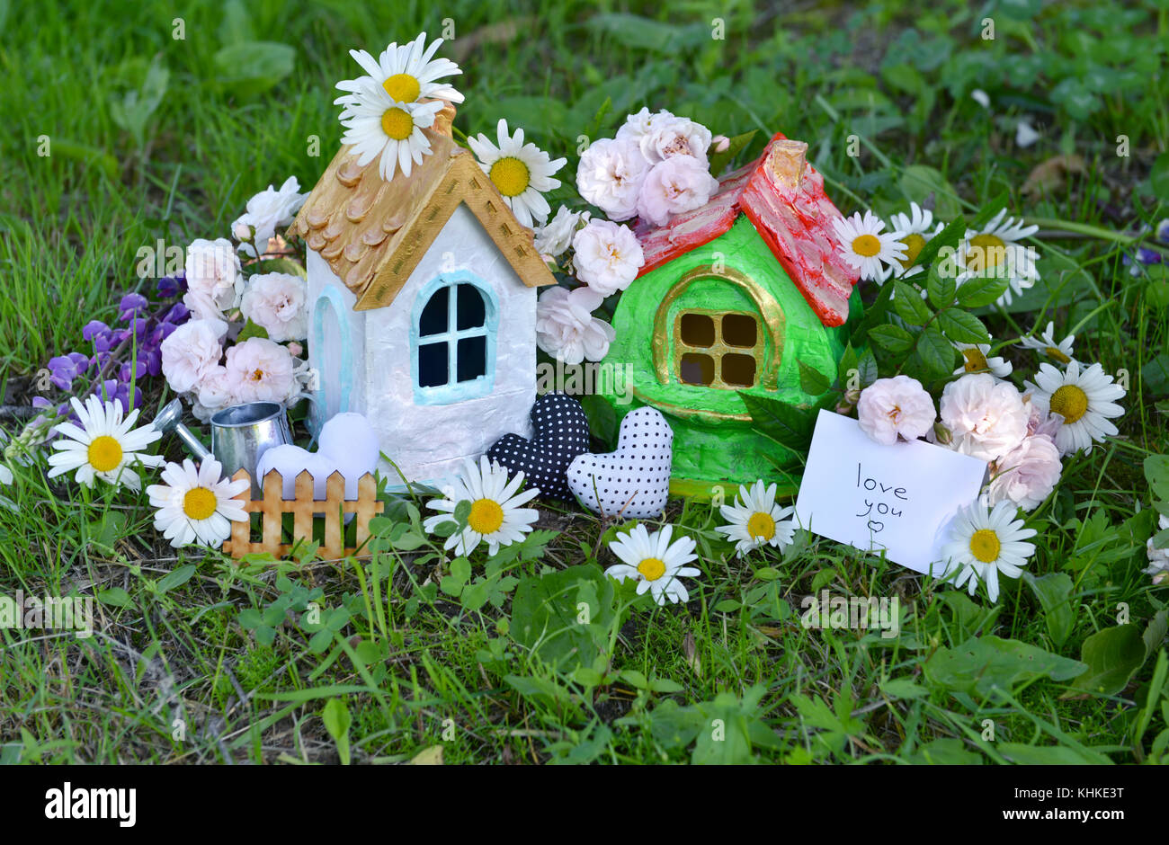 Two beautiful toy houses with note and text love you, cute decorations, roses and daisy flowers in the grass - Stock Image