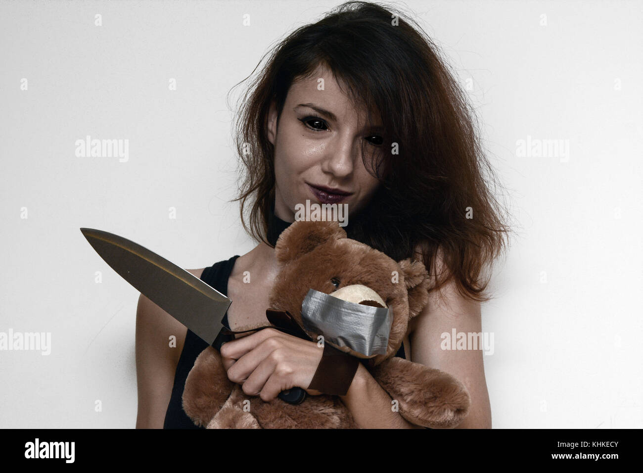 A demon female trying to kidnap and kill a teddybear Stock Photo