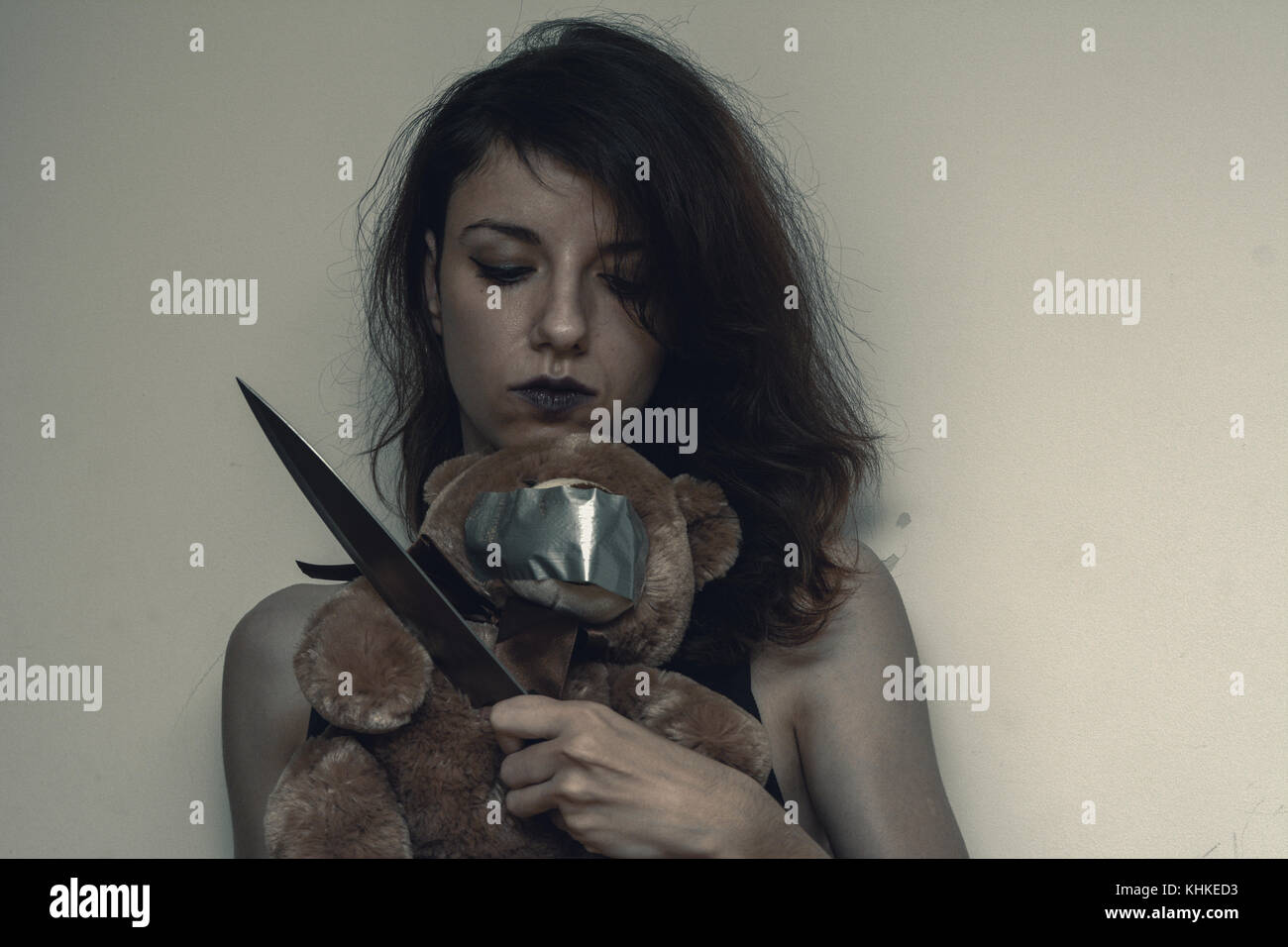 A demon female trying to kidnap and kill a teddybear - Stock Image