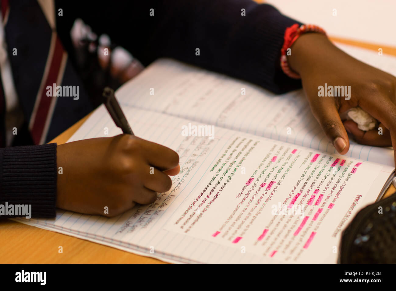 Secondary Education in the UK: close up of the hand of a pupil writing in their exercise book note books in an English - Stock Image