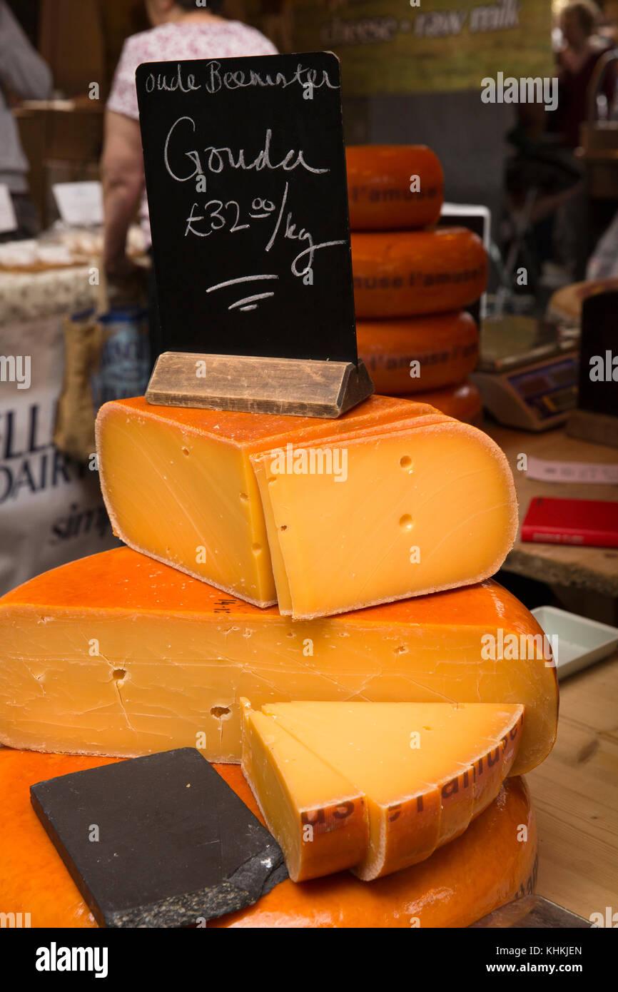 UK, London, Southwark, Borough Market, Mature Gouda cheeses displayed on Cheese stall - Stock Image