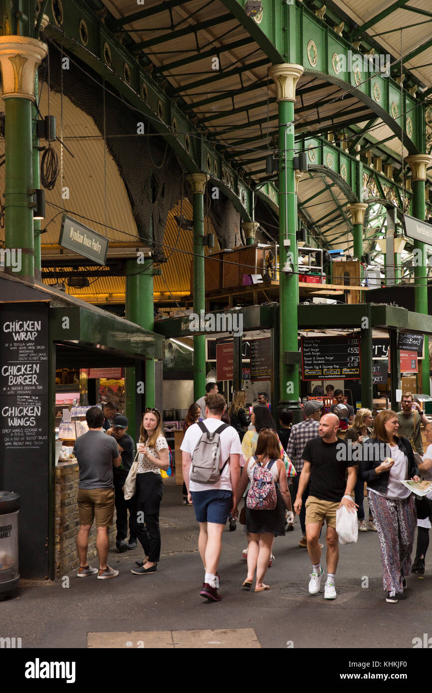 UK, London, Southwark, Borough Market, food stalls and visitors below railway arches - Stock Image