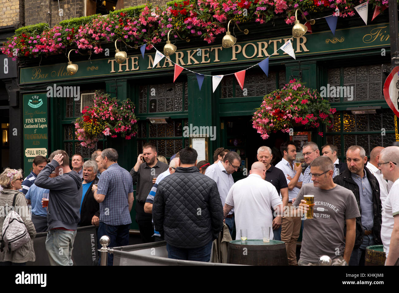 UK, London, Southwark, Stoney Street, drinkers below floral hanging baskets outside Market Porter pub - Stock Image