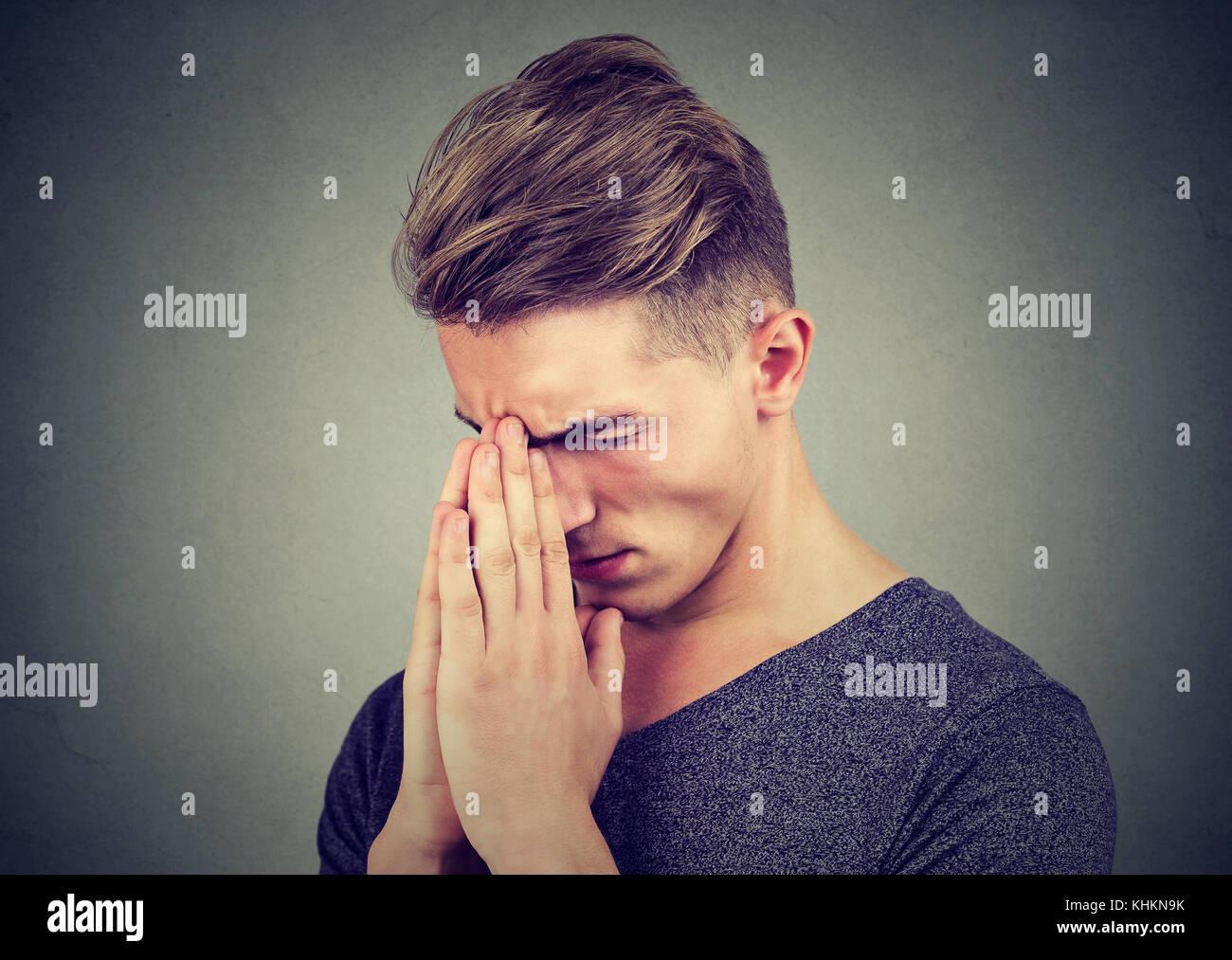 Sad man with tensed face expression praying - Stock Image