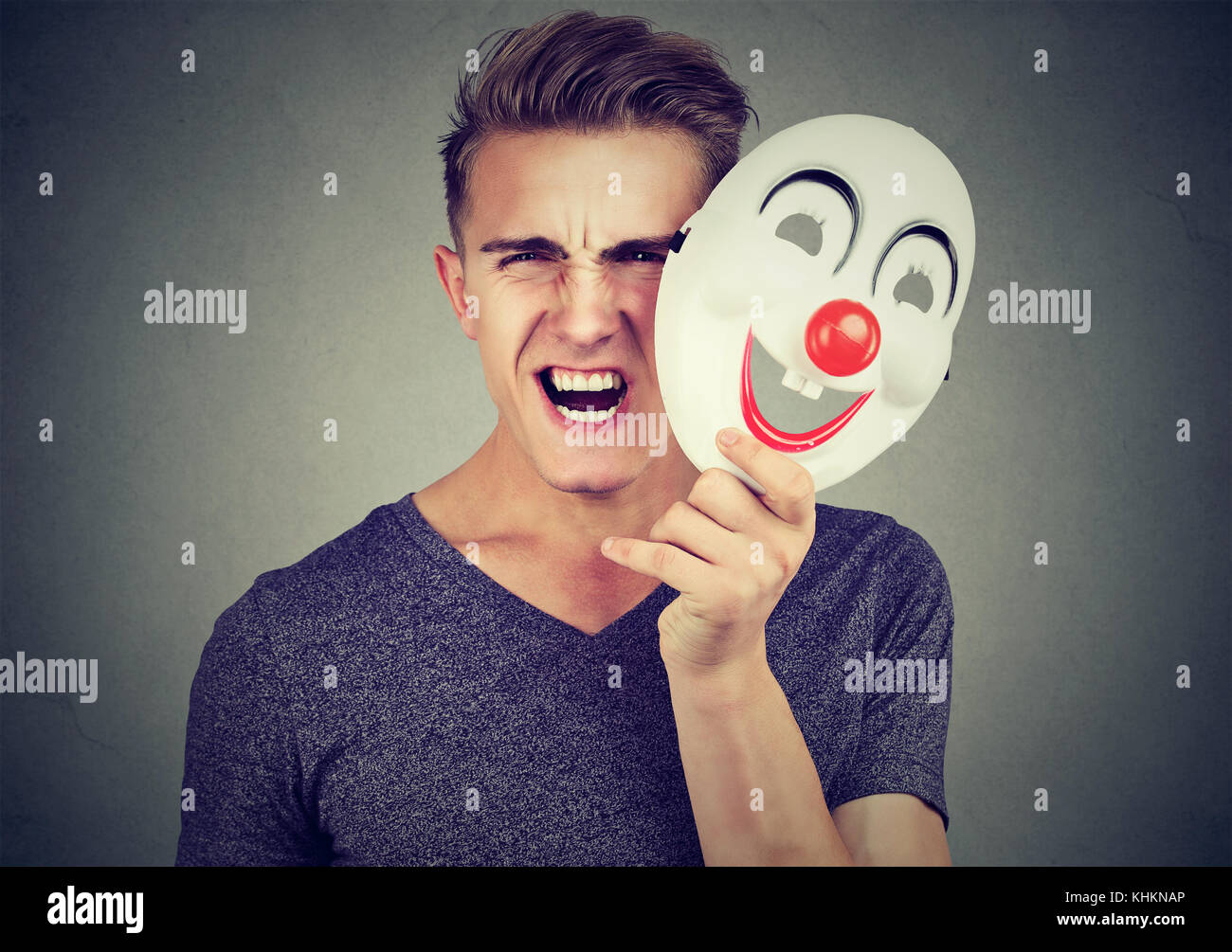 Portrait angry screaming man taking off a clown mask expressing happiness isolated on gray background. Human emotions Stock Photo