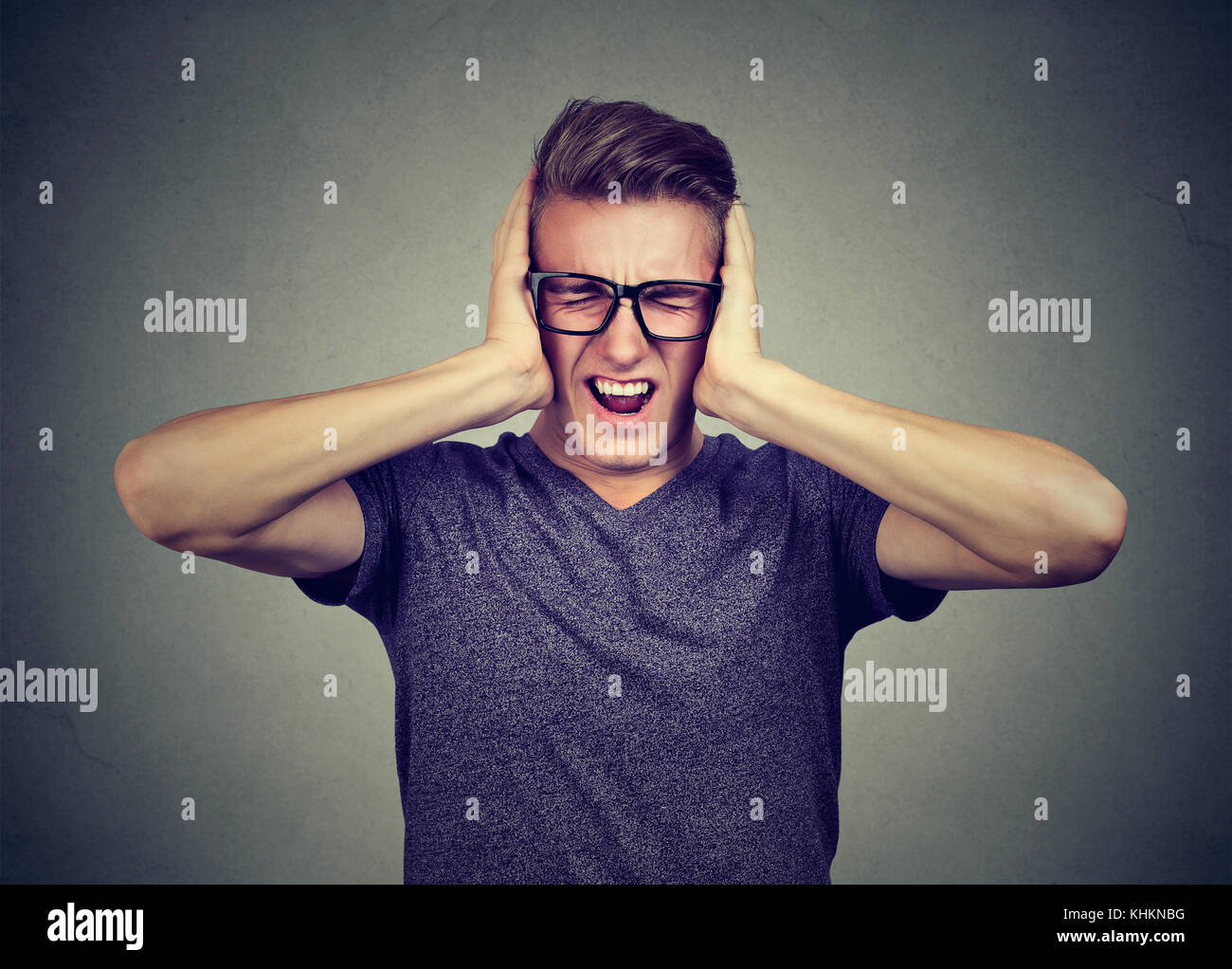 stressed man frustrated can't tolerate anymore loud noise. Negative human emotions - Stock Image