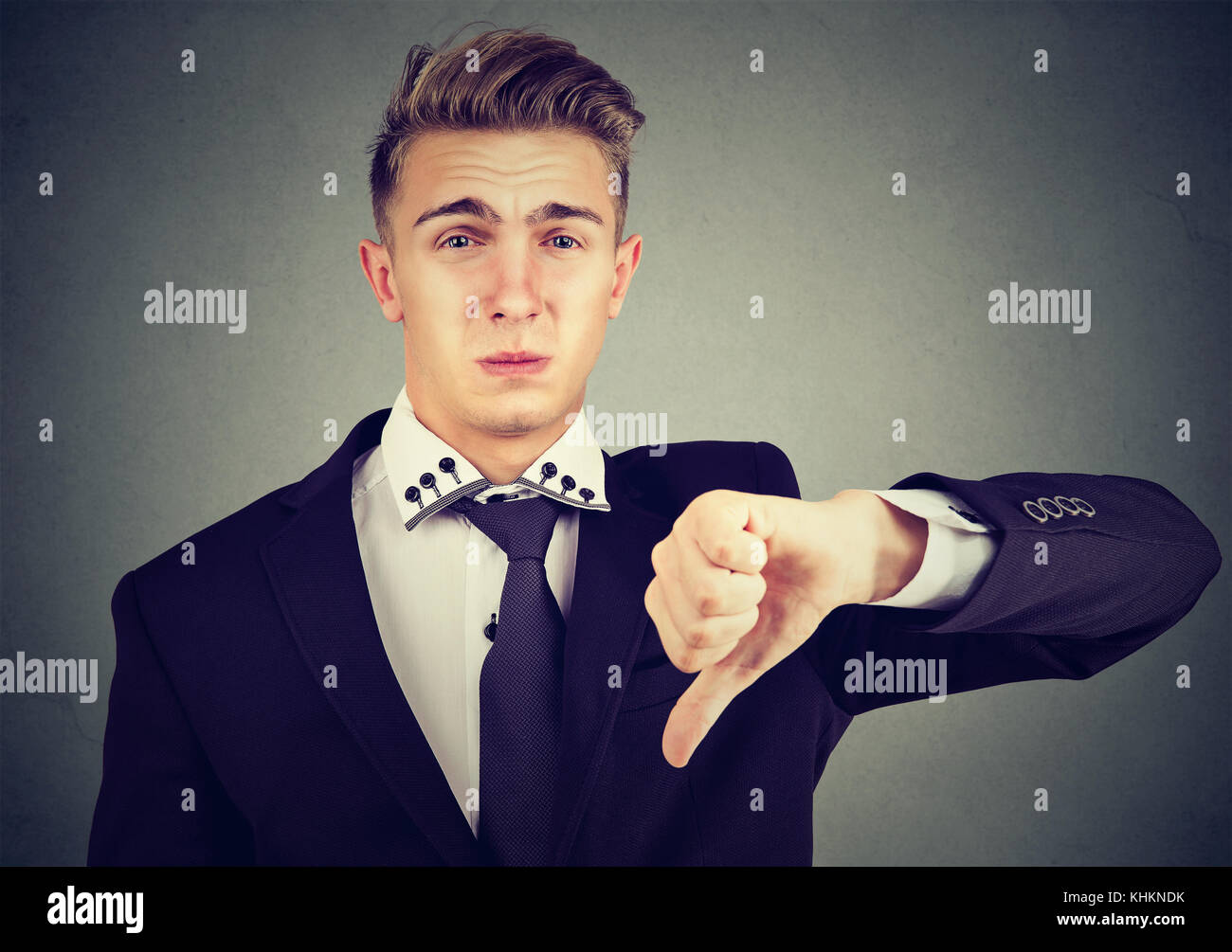 Angry disappointed young business man showing thumbs down sign, in disapproval isolated on gray background. Negative - Stock Image