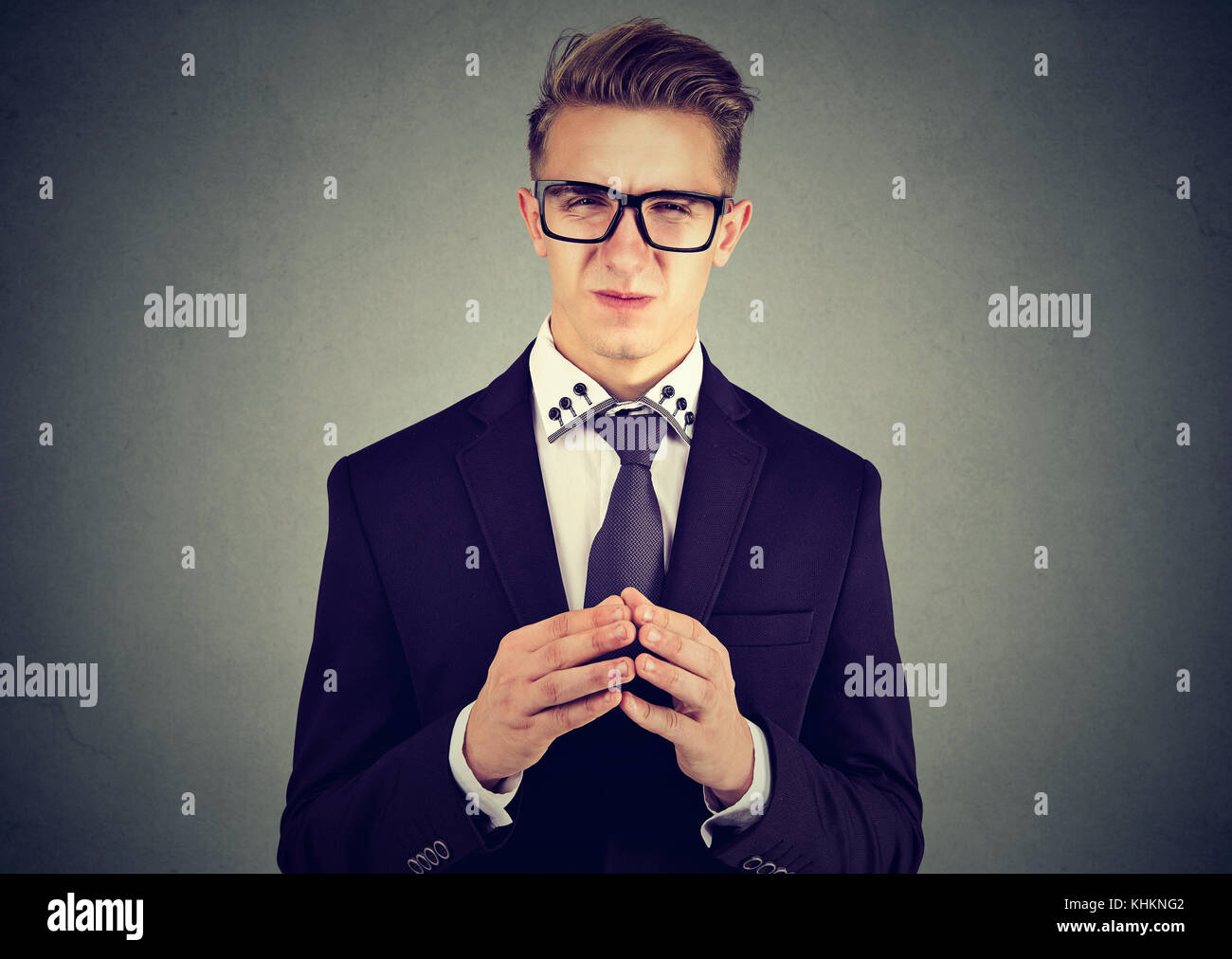 Sly business man in glasses looking at camera - Stock Image