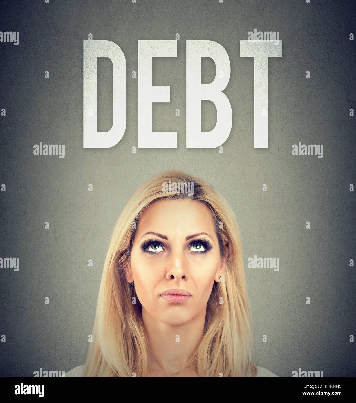 Stressed business woman under debt pressure - Stock Image