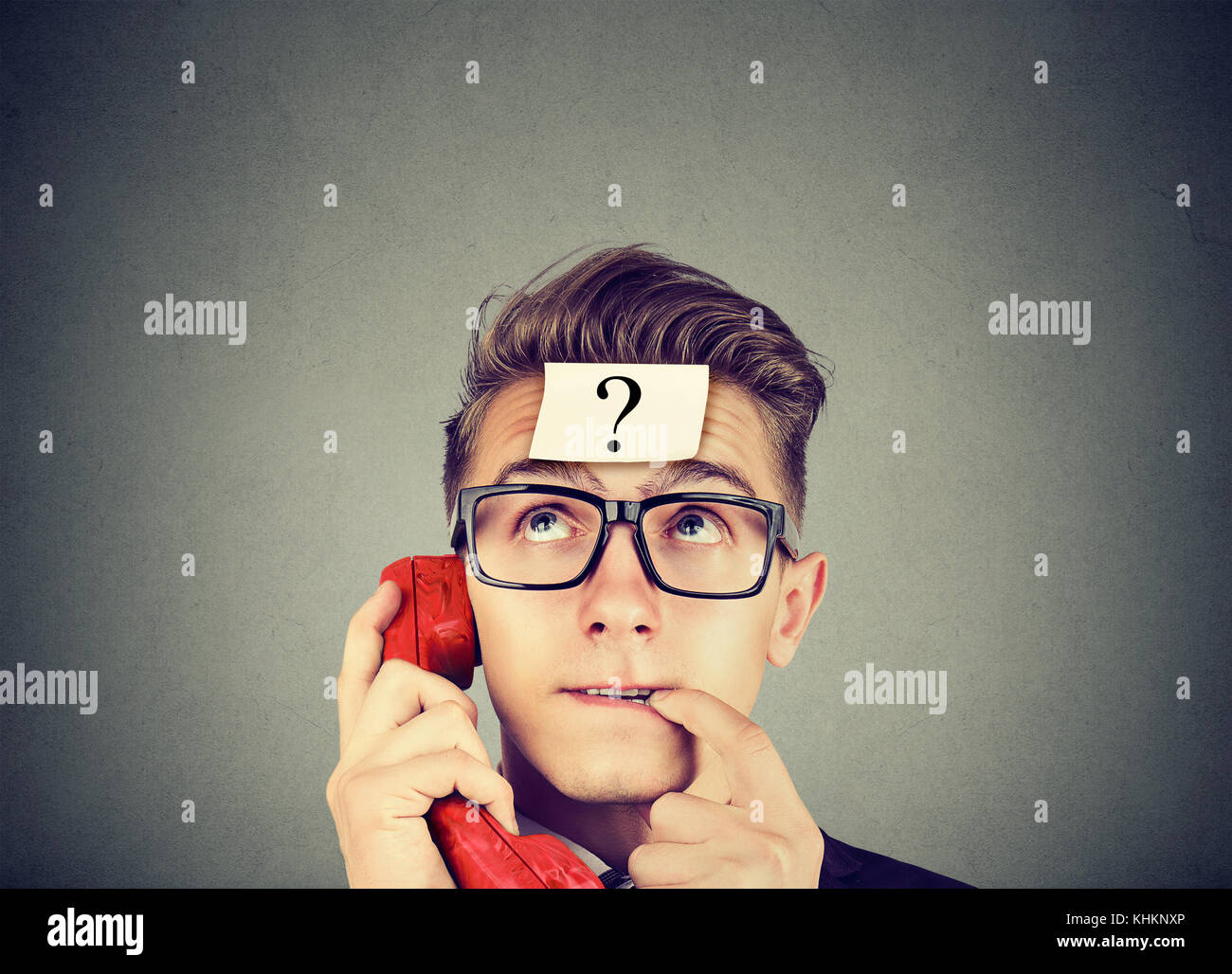 Perplexed young man with question mark having a telephone conversation - Stock Image