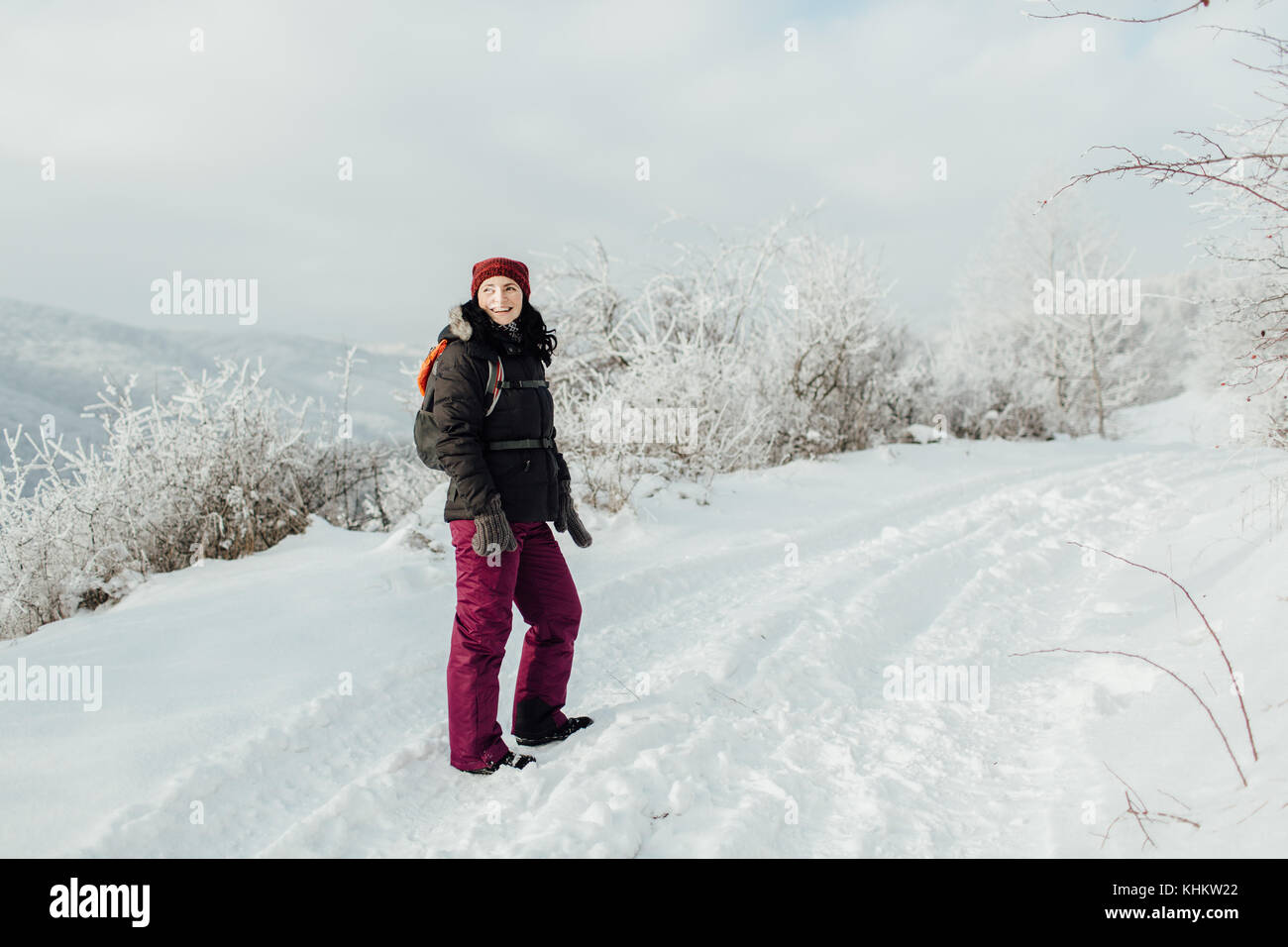 Happy female tourist standing on a snow trek and looking back - Stock Image