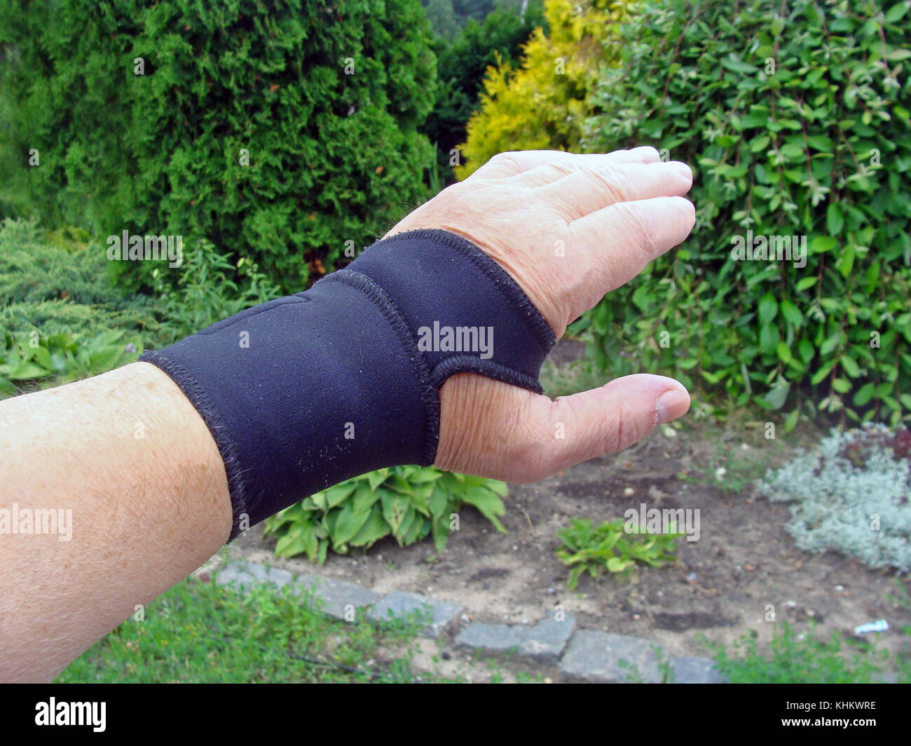 Hand with black color elastic bandage on wrist joint close up outdoor. - Stock Image