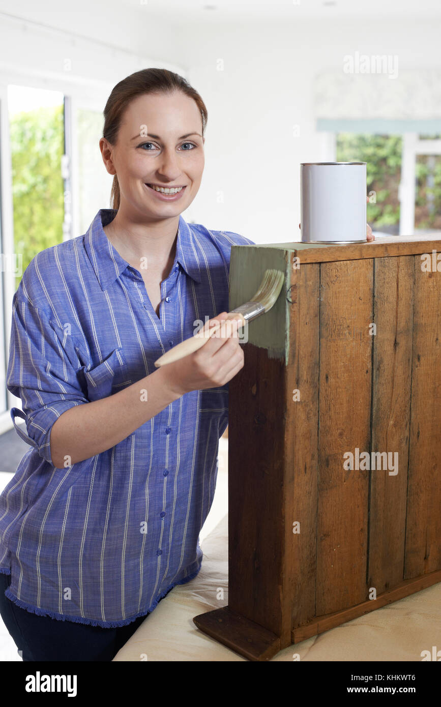 Woman Upcycling Wooden Cabinet At Home - Stock Image