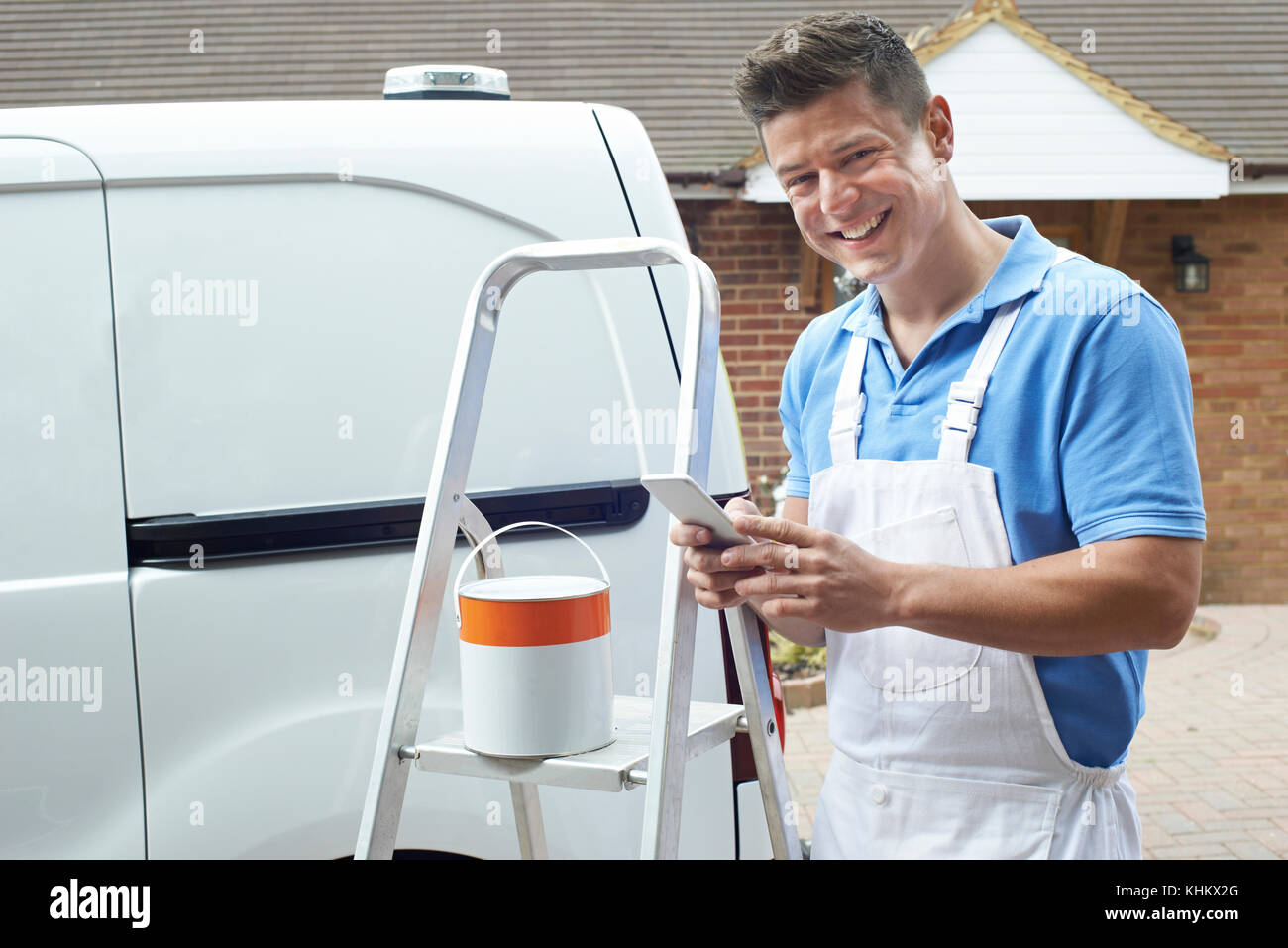 Decorator Using Mobile Phone Standing Outside Domestic Home - Stock Image