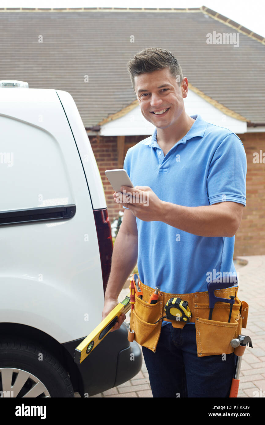 Builder With Van Checks Text Messages On Mobile Phone Outside House - Stock Image