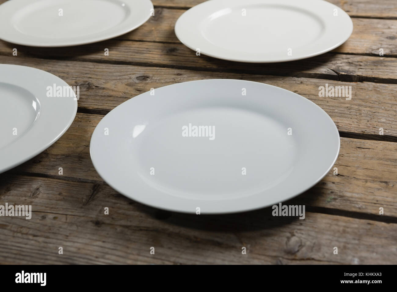 Empty white plates on wooden table - Stock Image