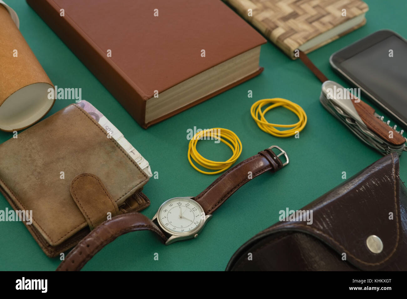 Close-up of disposable glass, wallet, organizer, wristwatch, pocketknife, mobile phone and sunglasses case on green - Stock Image