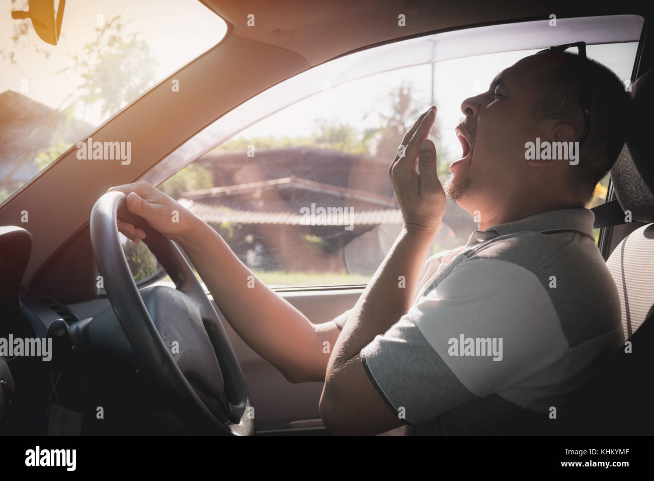 Sleepy yawning man driving car in traffic after long hour drive. Man falling asleep in car. - Stock Image