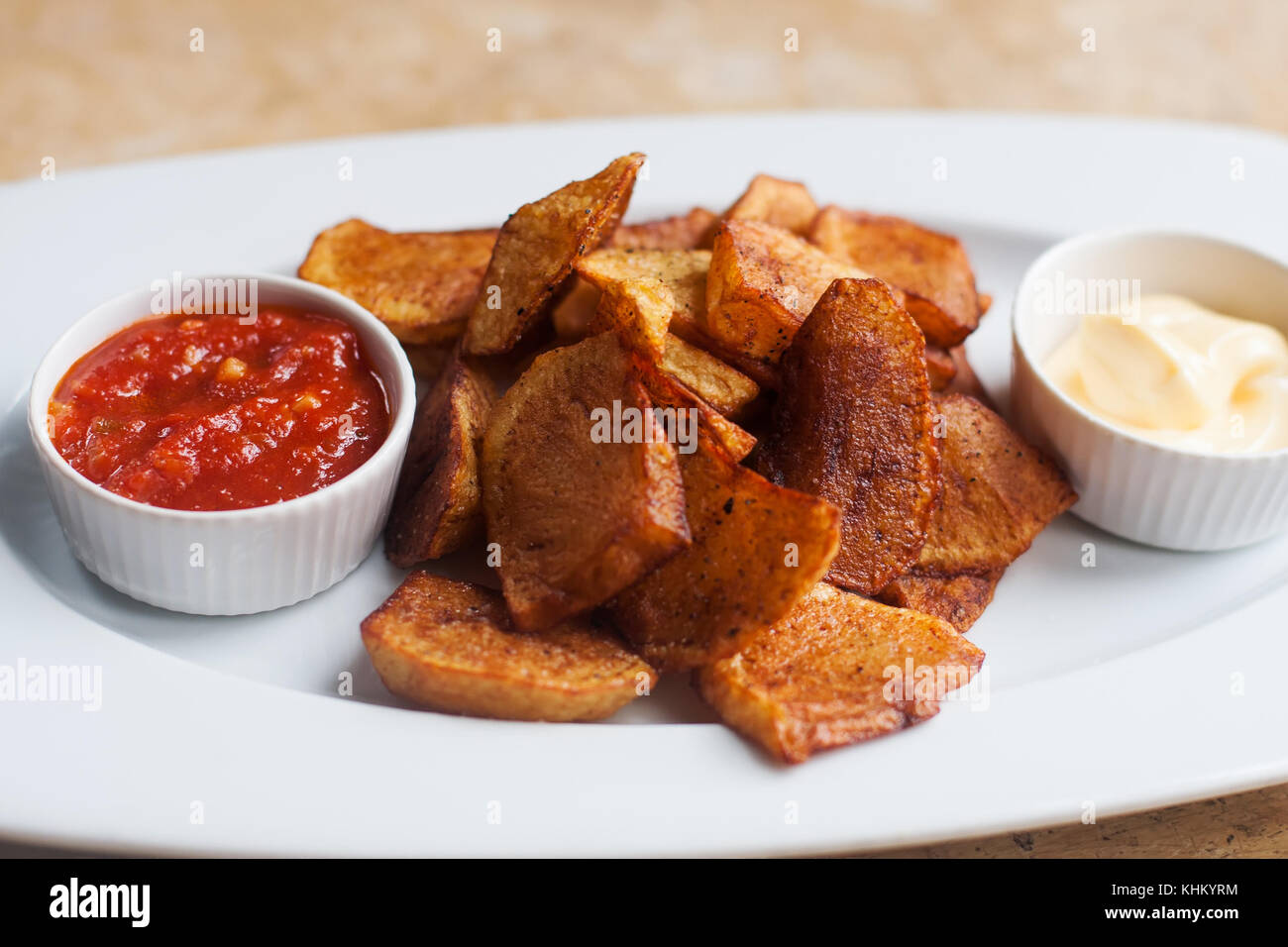 Spanish cuisine food tapas Patatas bravas, fried potato with red tomato white aioli sauce. Selective focus photo Stock Photo