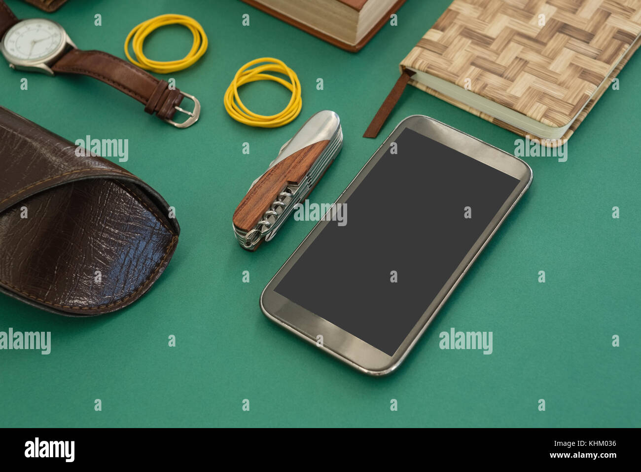 Close-up of organizer, wristwatch, pocketknife, mobile phone and sunglasses case on gr - Stock Image