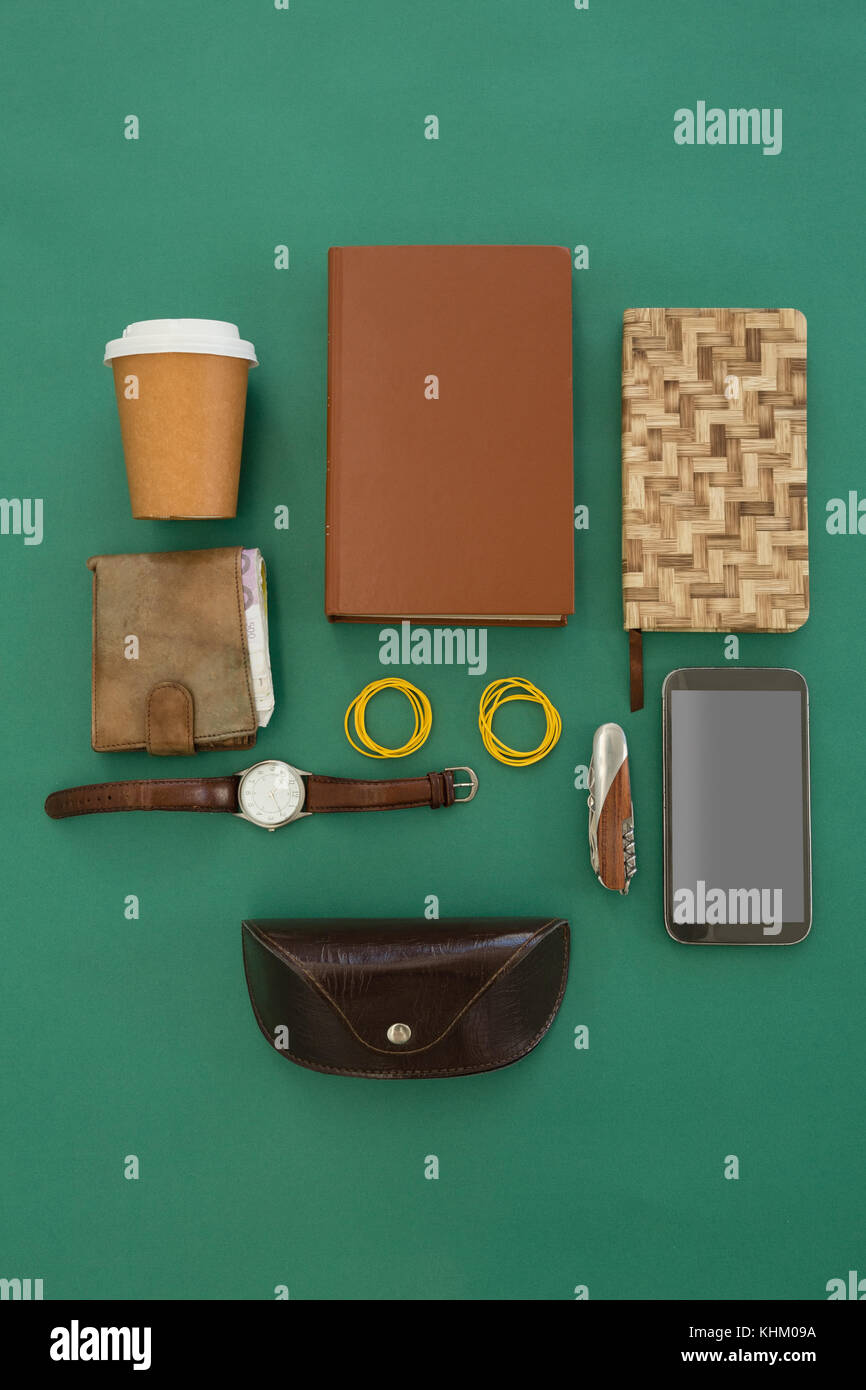 Overhead of disposable glass, organizer, wristwatch, pocketknife, mobile phone and sunglasses case on green background - Stock Image
